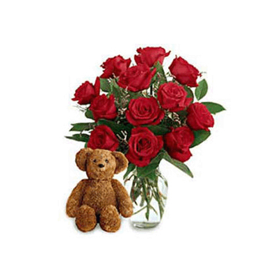 red roses in vase and a cuddly teddy bear